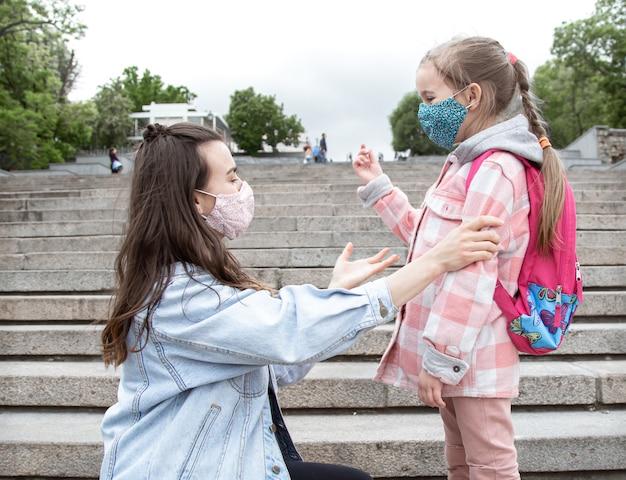 Mamma con la sua piccola figlia, una studentessa, sui gradini sulla strada per la scuola. coronavirus concetto di educazione pandemica.