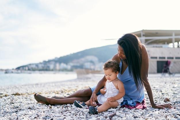 La mamma con una bambina si siede sulla spiaggia e le mostra dei sassi