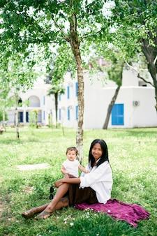La mamma con una bambina si siede su una coperta sul prato vicino a un albero
