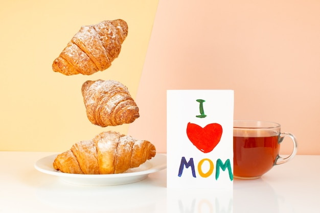 Mamma con carta cuore rosso e croissant levitanti su un piatto con una tazza da tè su sfondo pastello
