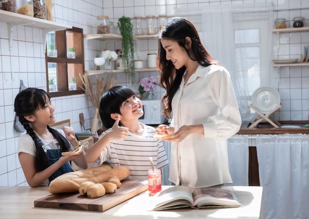 La mamma con il figlio e la figlia mangiano l'igname con pane