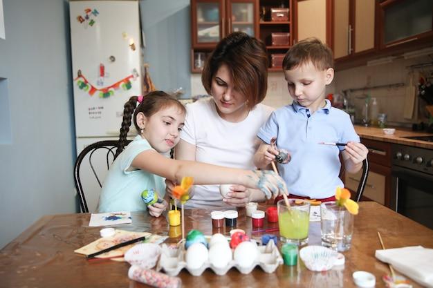 La mamma con due bambini decora le uova di pasqua seduti a tavola a casa in cucina