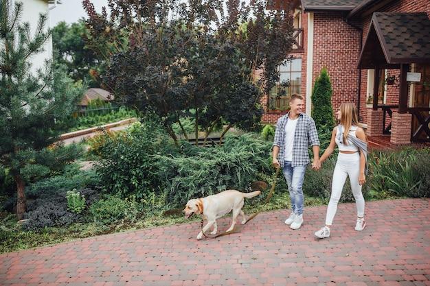 Momento di riposo! giovane famiglia attraente che cammina il labrador vicino alla casa. belle coppie vicino a casa moderna con il cane al guinzaglio.