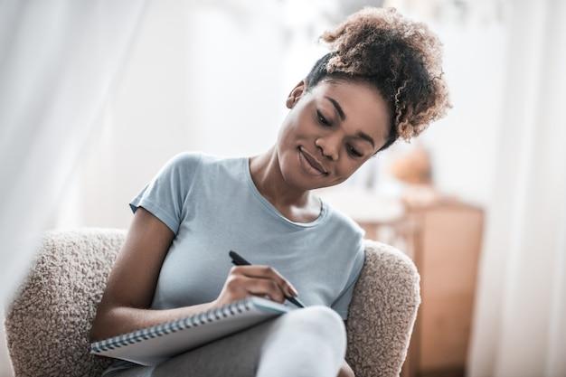 Momenti di ispirazione. sorridente giovane donna dalla carnagione scura con la scrittura di concentrazione con la penna in taccuino che si siede nella stanza luminosa a casa