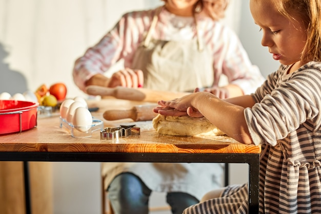 Mamma che aiuta la figlia del bambino a rotolare la pasta per i biscotti o la torta fatti in casa. famiglia di due generazioni femminili che gode del processo di cottura insieme in cucina, nell'atmosfera domestica