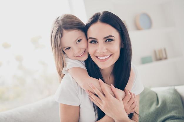 Mamma che abbraccia tenendo sulle spalle piccola figlia in casa casa al chiuso