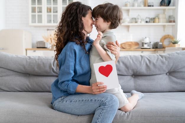 Mamma e bambino felici il giorno della madre o il compleanno bambino allegro ragazzo e madre single che si abbracciano