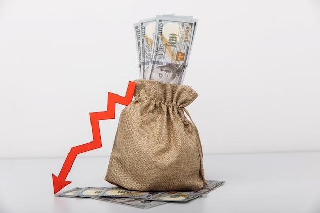 Borsa dei soldi e freccia rossa verso il basso. concetto di difficoltà economiche.
