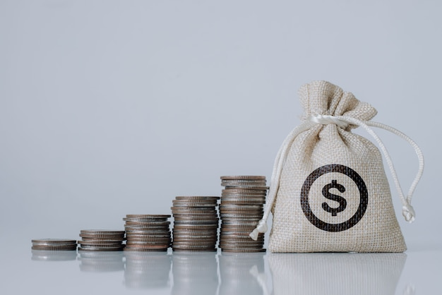 Borsa di denaro e monete d'oro impilate con crescere sul legno bianco in studio per prestiti a investimenti pianificati nel concetto futuro.