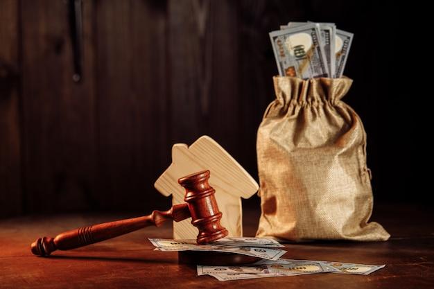Borsa di denaro con tasse per la casa in contanti e il martelletto del giudice sul concetto di pagamento immobiliare
