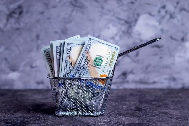 Banconote dei soldi in un setaccio grasso profondo per l'apertura degli alimenti a rapida preparazione di una piccola impresa su un fondo grigio