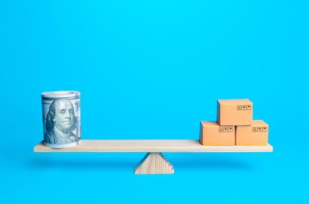 Fascio di denaro di dollari e scatole sulla bilancia bilancia commerciale e potere d'acquisto commercio