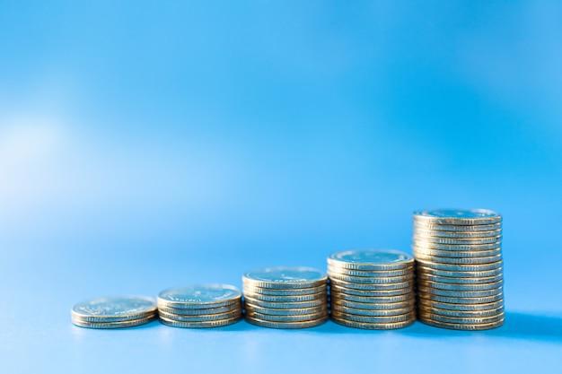 Denaro, affari e concetto di rischio. primo piano della pila di monete su fondo blu con lo spazio della copia.