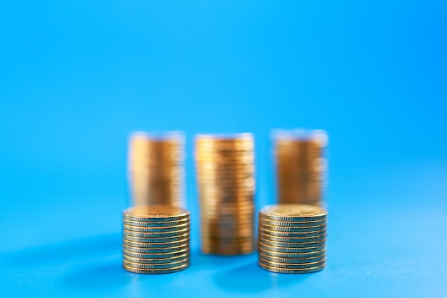 Denaro, affari e concetto di rischio. primo piano della pila di monete d'oro sull'azzurro con lo spazio della copia.