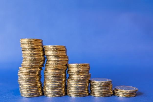 Denaro, affari e concetto di risparmio. primo piano di cinque pile di monete d'oro su sfondo blu.