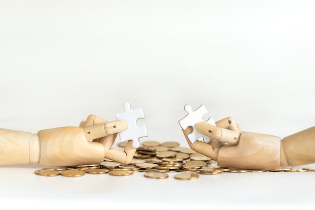 Denaro e soluzione aziendale concetto. primo piano della mano in legno modello azienda puzzle jigsaw sulla pila di monete d'oro e sfondo bianco.