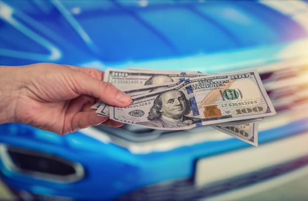 Soldi per comprare la macchina nuova. concetto finanziario. dollaro in mano