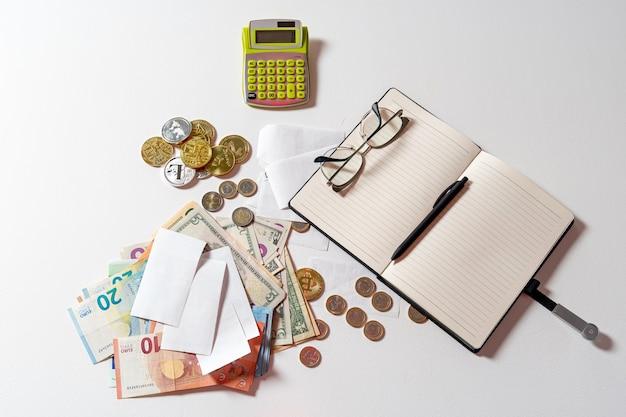 Denaro, calcolatrice, penna, carta, taccuino e occhiali su sfondo bianco, concetto di analisi finanziaria, calcolo del budget, disposizione piatta, primo piano