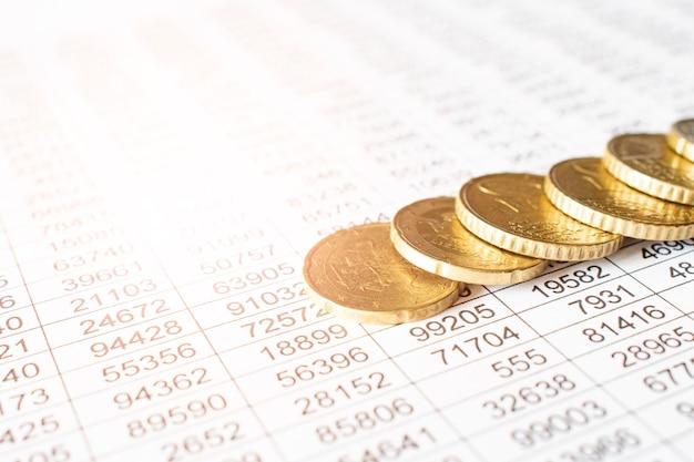 Moneta di denaro sul foglio del rapporto contabile, risparmio di denaro o concetto finanziario.