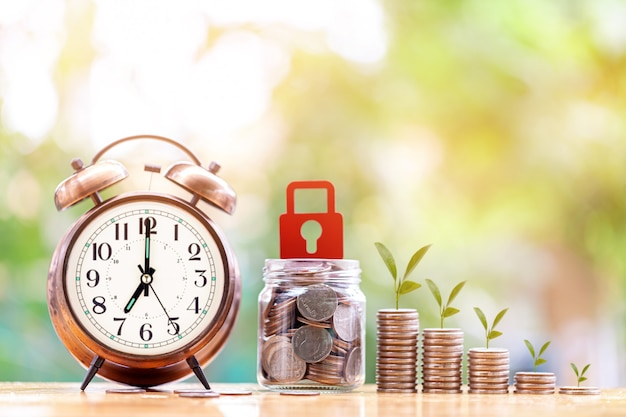 Grafico crescente della pila di monete dei soldi con la sveglia per trarre profitto dal concetto di investimento e finanza