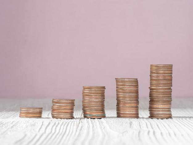 Pila della moneta dei soldi su fondo di legno bianco