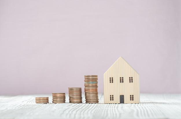Pila della moneta dei soldi con il modello della casa di legno su fondo di legno bianco