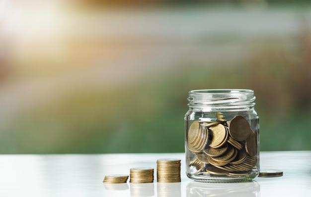 Pile della moneta dei soldi e vaso di vetro con le monete