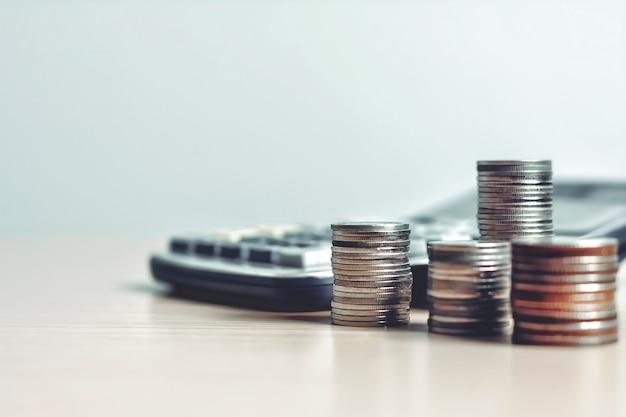Le monete dei soldi si impilano con la calcolatrice e alcuni articoli di cancelleria su un tavolo di legno con spazio per le copie