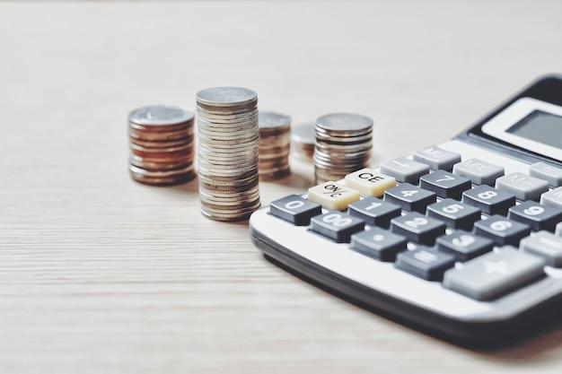 Pila di monete di denaro con calcolatrice e alcuni elementi di cancelleria sul tavolo di legno