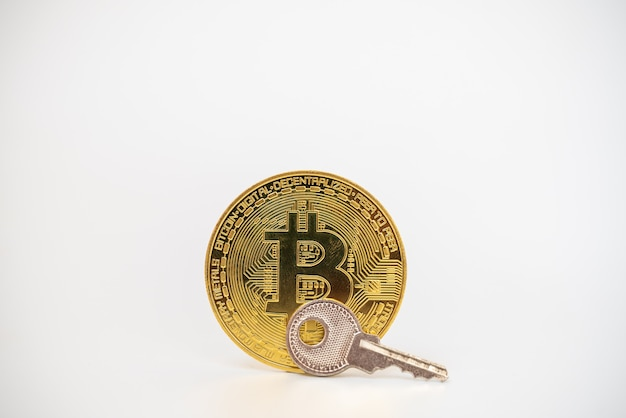 Denaro, criptovaluta finanziaria e concetto di sicurezza. moneta bitcoin in oro con chiave d'argento su sfondo bianco.