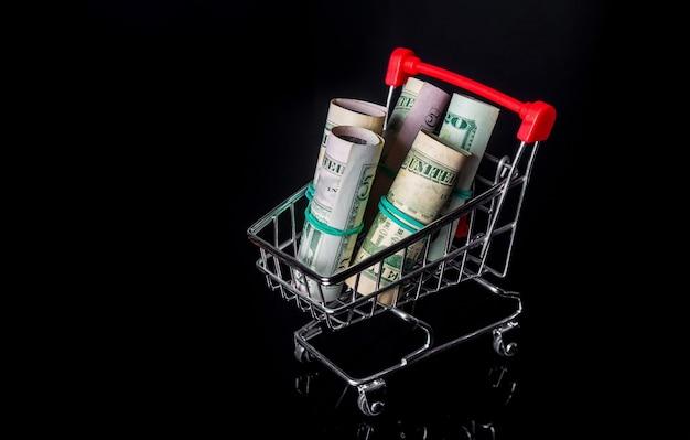 Denaro o dollari arrotolati in un tubo in un carrello su sfondo nero. vendite e concetto di acquisto. spazio pubblicitario gratuito