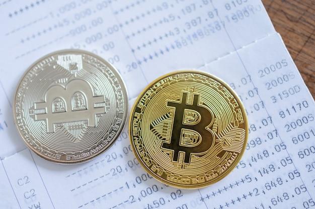 Concetto di denaro, finanza e criptovaluta. primo piano di monete bitcoin in oro e argento sul libretto bancario su tavolo in legno d'oro.
