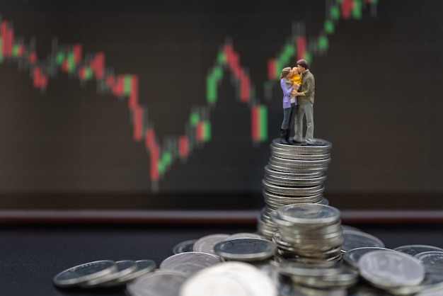 Denaro, finanziario, investimento aziendale e concetto di famiglia. genitore e figlio le figure in miniatura si abbracciano e si baciano insieme in piedi su una pila di monete con un grafico a candela come sfondo.
