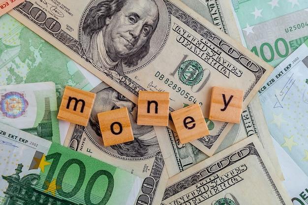 Iscrizione di denaro su cubi di legno sulla trama di dollari americani e banconote in euro