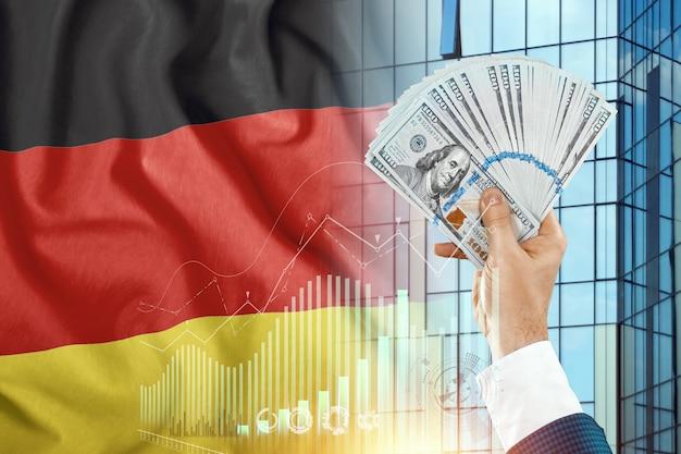 Soldi in mano di un uomo sullo sfondo della bandiera della germania. il reddito di nemtsov. la condizione finanziaria dei residenti in germania, tasse, prestiti, mutui. debito statale del paese.