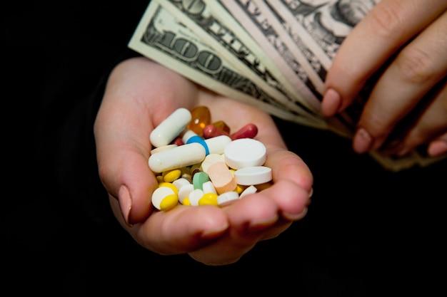 Soldi e pillole nelle mani, isolate sul nero. sprecare troppi soldi in medicinali. concetto di tossicodipendenza.