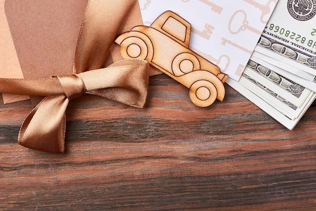 Soldi e fiocco di nastro. automobile di pirografia e carta bianca. regalo elegante e ricco.