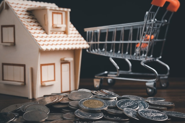 Idea imprenditoriale di risparmio di denaro, monete impilate sul tavolo di legno con casa sfocata e carrello.