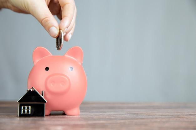 Risparmio di denaro per l'acquisto di una nuova casa nel salvadanaio rosa, immobili, mutui, prestiti, concetto di affari con spazio per lo spazio della copia del testo sulla tavola di legno