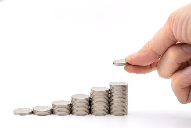 Denaro e concetto di risparmio. primo piano della mano dell'uomo che tiene due monete e mette in cima alla fila di monete d'argento dello stack su sfondo bianco.