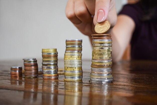 Concetto di risparmio di denaro, predefinito dalla mano femminile che mette i soldi dalla pila di monete.