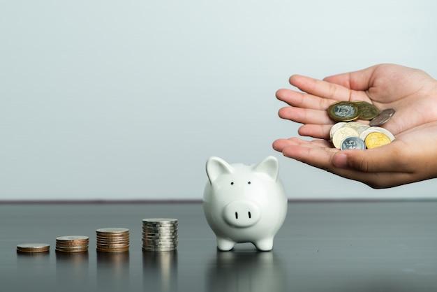 Il concetto di donazione e di risparmio di denaro, bambino ha messo i soldi sul porcellino salvadanaio bianco sveglio