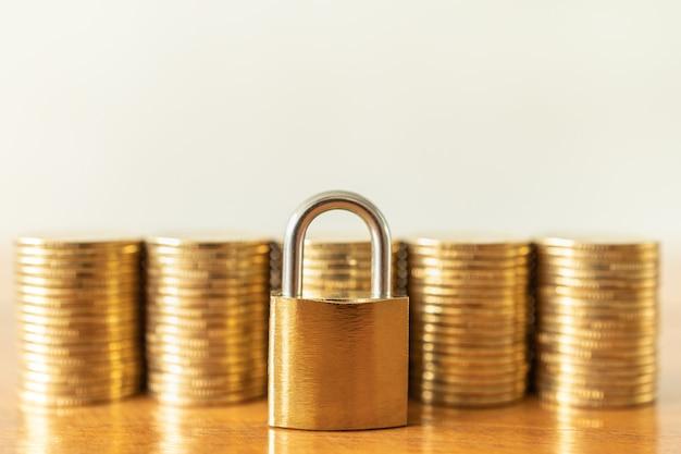 Concetto di denaro e sicurezza primo piano della serratura a chiave principale dorata con una pila di monete d'oro