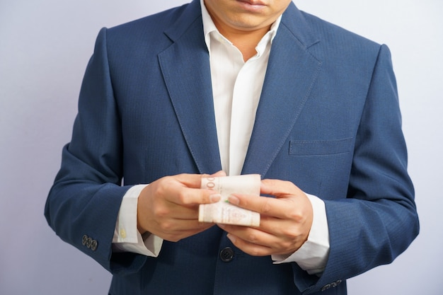 Soldi in tailandia tengono a portata di mano l'uomo d'affari che afferra indossa un abito blu