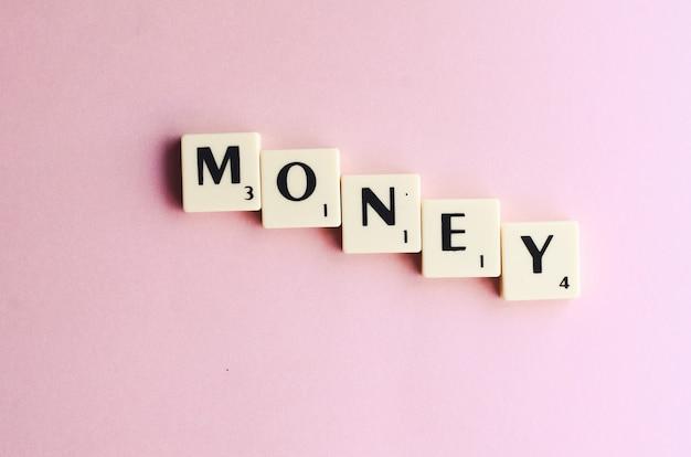 Parola di denaro su cubi di legno su sfondo rosa