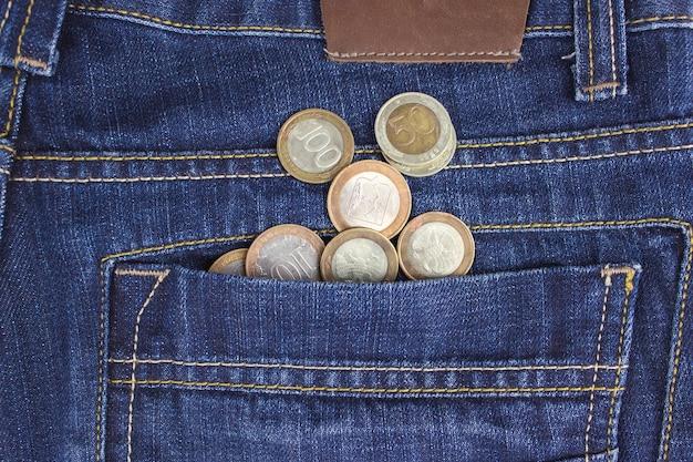 Soldi in tasca. monete in tasca dei jeans. il concetto di paghetta. contanti. concetto di affari.