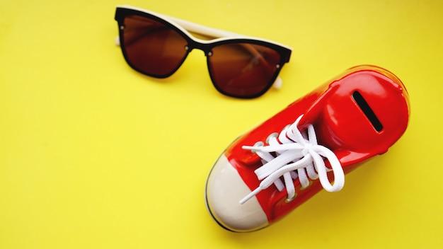 Salvadanaio a forma di scarpe da ginnastica. occhiali da sole su sfondo giallo. il concetto di risparmio in vacanza e vacanze estive. risparmia denaro