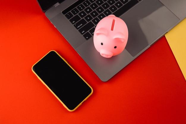 Salvadanaio vicino a laptop e smartphone, posto per il testo. finanza e concetto di bilancio. salvadanaio in colore rosa con gadget e articoli di cancelleria su sfondo colorato.