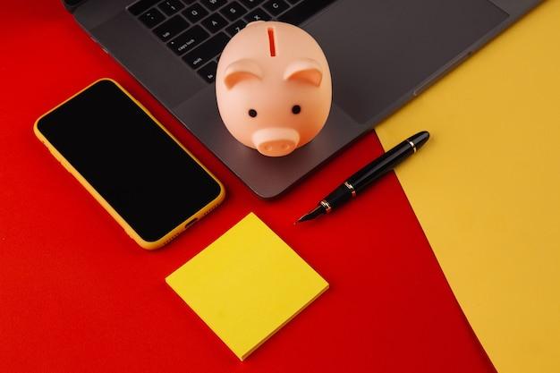 Salvadanaio vicino a laptop e smartphone con nota adesiva, posto per il testo. finanza e concetto di bilancio. salvadanaio in colore rosa con gadget e articoli di cancelleria su sfondo colorato.