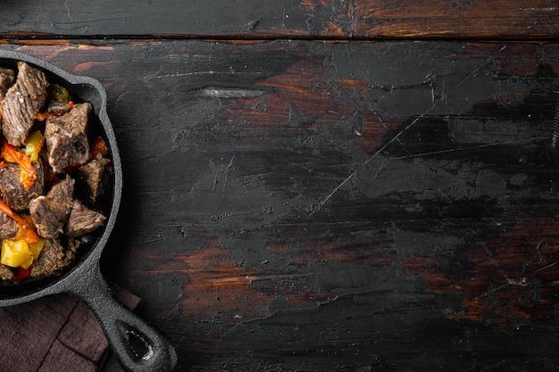 Manzo mongolo, pezzi di manzo stufato in salsa di soia set, in padella in ghisa, sul vecchio tavolo in legno scuro, vista dall'alto laici piatta